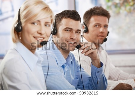 Happy young customer service operators receicving calls on headset, looking at camera, smiling.