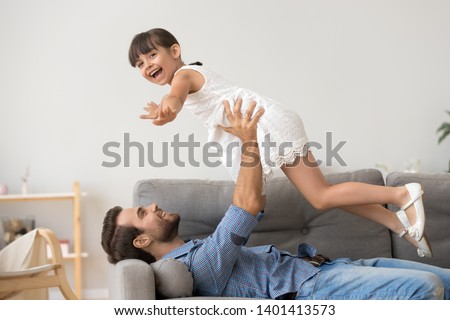 Happy young dad lie on couch play with excited cute little daughter holding her in hands fly up in air, smiling father relax have fun with funny preschooler girl kid, play games entertain at home