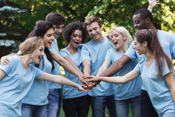 Happy young diverse volunteers preparing for work, join hands in park. Volunteering and teambuilding concept, copy space