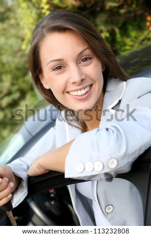 Happy young driver standing by car