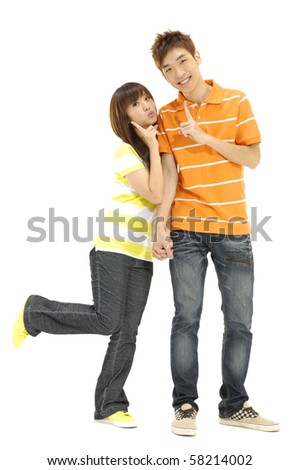 Happy young embracing couple standing on full length over white