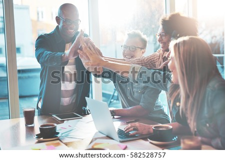 Happy young entrepreneurs in casual clothes at cafe table or in business office giving high fives to each other as if celebrating success or starting new project