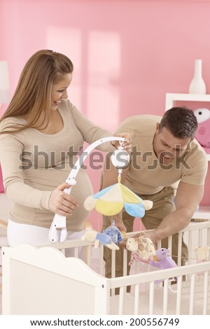 Happy young expecting couple equipping baby's cot.