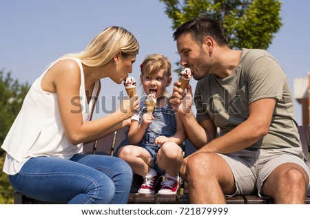 Happy young family eating ice cream and having fun outside