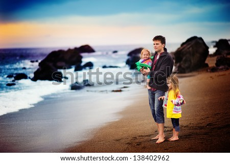happy young family father and two daughters have fun on beach run and jump at sunset