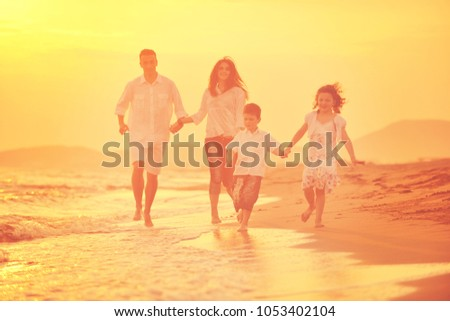 happy young family have fun on beach run and jump  at sunset #1053402104