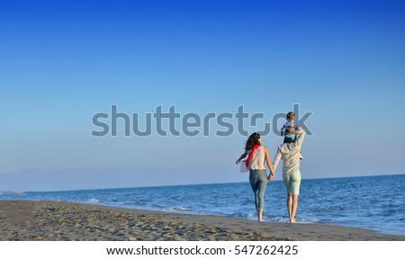 happy young family have fun on beach run and jump at sunset #547262425