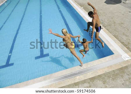 happy young family have fun on swimming pool  at summer vacation running and jumping in the pool
