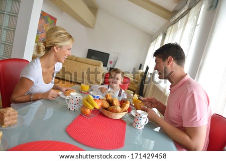 happy young family have healthy breakfast at kitchen with red details on bright morning light - stock photo