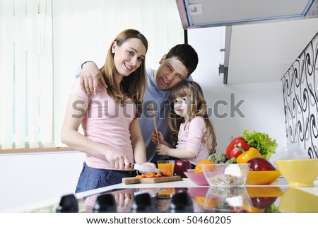 happy young family have lunch time with fresh fruits and vegetable food in bright kitchen