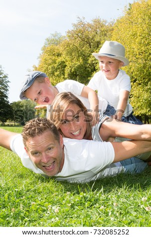 Happy young family having fun outdoors in summer. Mother, father and their cute little son are playing in the sunny garden. Happy parenthood and childhood concept #732085252