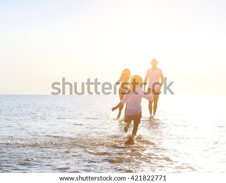 Happy young family having fun running on beach at sunset. Family traveling concept #421822771