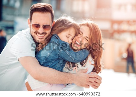 Happy young family in city street,having fun.