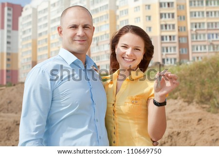 happy young family in front of new home - stock photo