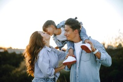 happy young family in the park at sunset. happy boy sits on dad's shoulders. mom kisses her son. sun rays on faces. young stylish family in casual outdoor clothes