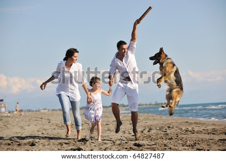 happy young family in white clothing have fun and play with beautiful dog at vacations on beautiful beach - stock photo