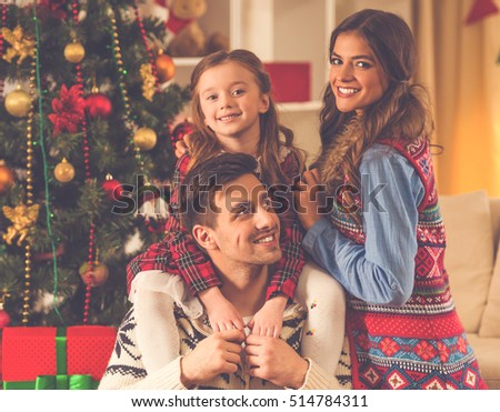 Happy young family is hugging and smiling while celebrating Christmas at home