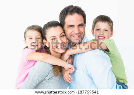 Happy young family looking at camera together on white background