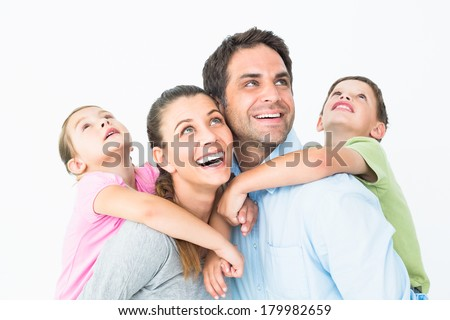 Happy young family looking up together on white background