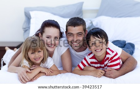 Happy young family lying in bed together