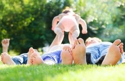 Happy young family lying on green grass outdoors in the summer park