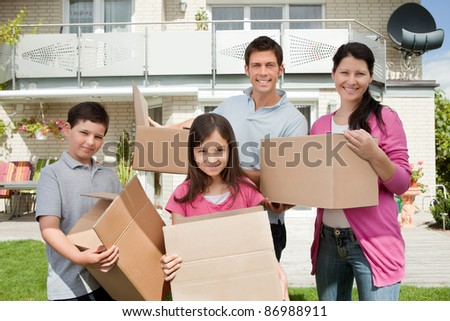 Happy young family moving into new home carrying boxes