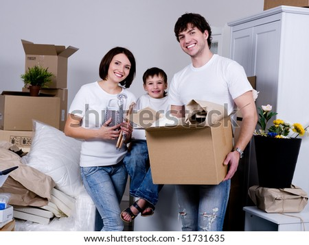 Happy young family moving to the new flat - indoors - stock photo
