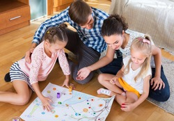 Happy young family of four playing at board game in domestic interior