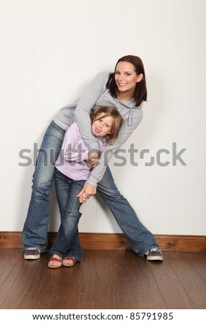 Happy young family of mum and daughter with hug and embrace with big laughing smiles. Both wearing denim jeans and hoodie.