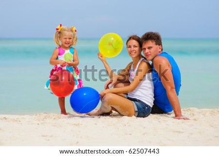 happy young family of three have a party with colorful balloons on tropical beach