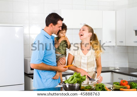 happy young family of three in home kitchen