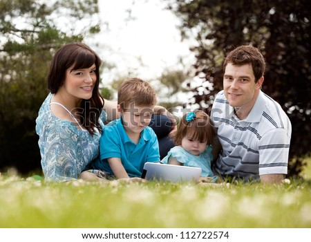 Happy young family outdoors with digital tablet