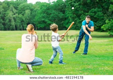 Happy Young Family Playing Baseball At Park