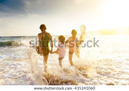 happy young family playing on beach at sunset #435241060