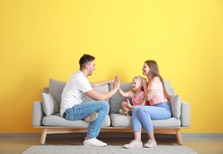 Happy young family playing while sitting on sofa near color wall