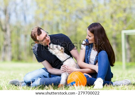 happy young family playing with a dog licking his owner in face as a sign of affection