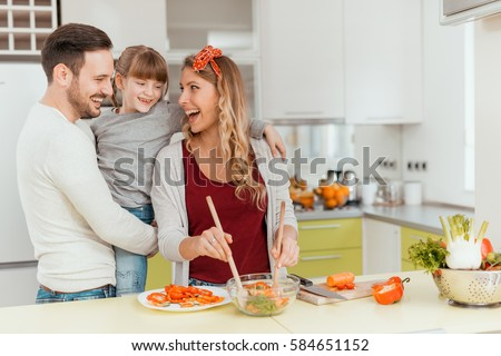 Happy young family preparing lunch in the kitchen and enjoying together. #584651152