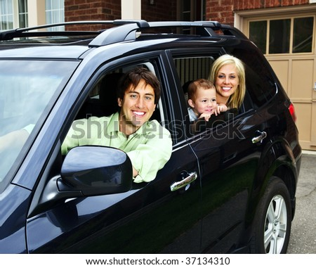 Happy young family sitting in black car looking out windows