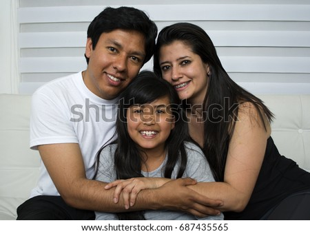 Happy young family sitting on sofa. #687435565