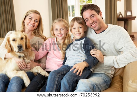Happy young family sitting on sofa holding a dog - stock photo