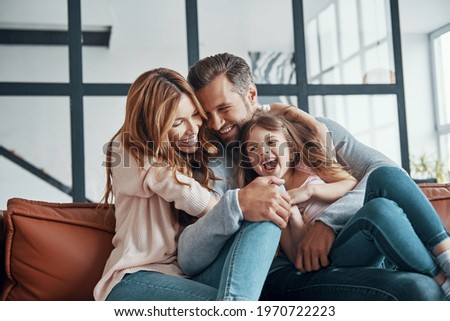 Happy young family smiling and embracing while bonding together at home