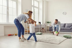 Happy young family spending leisure time at home, having fun and engaging their small child in sport activities. Mom and dad with little son playing game with inflatable ball in spacious living-room