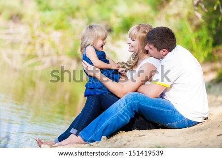 happy young family spending time outdoor on a lake