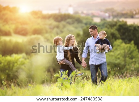 Happy young family spending time together outside in green nature. - Shutterstock ID 247460536