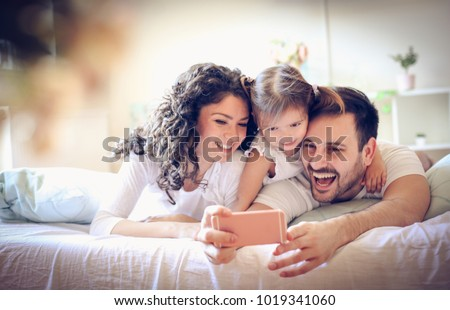 Happy young family take a self portrait with smart phone.