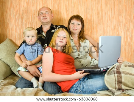 Happy young family using  laptop in the living-room