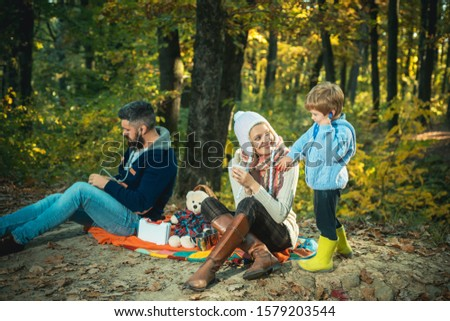 Happy young family walking at beautiful fall autumn nature. Mother wearing a ear-flapped hat and plaing with her son a doctor game. Little cute boy is smiling. Family concept