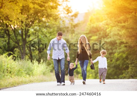 Happy young family walking down the road outside in green nature.
