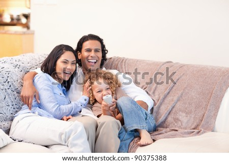 Happy young family watching television together