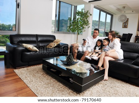 happy young family wathching flat tv at modern home indoor - stock photo